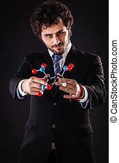 businessman holding a tnt molecular structure