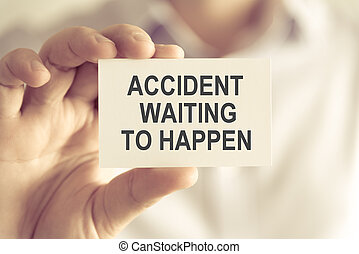 Businessman holding ACCIDENT WAITING TO HAPPEN message card