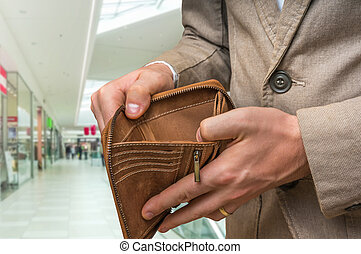Businessman holding an empty wallet in shopping centre