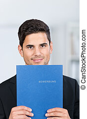 Businessman Holding Application File In Office