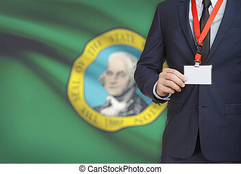 Businessman holding badge on a lanyard with USA state flag on background - Washington