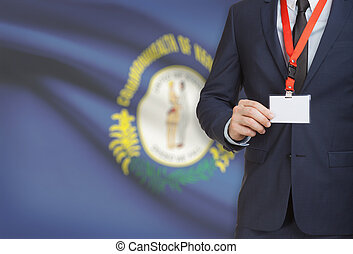 Businessman holding badge on a lanyard with USA state flag on background - Kentucky