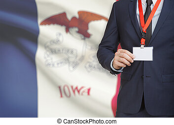 Businessman holding badge on a lanyard with USA state flag on background - Iowa