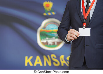 Businessman holding badge on a lanyard with USA state flag on background - Kansas