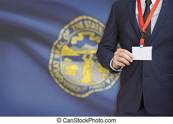 Businessman holding badge on a lanyard with USA state flag on background - Nebraska