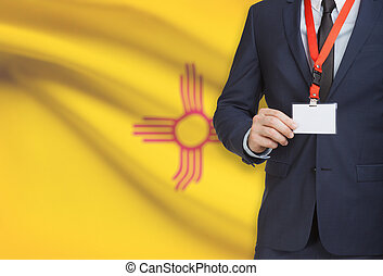 Businessman holding badge on a lanyard with USA state flag on background - New Mexico