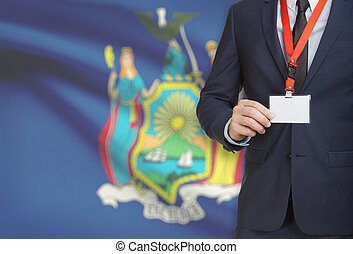 Businessman holding badge on a lanyard with USA state flag on background - New York