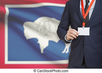 Businessman holding badge on a lanyard with USA state flag on background - Wyoming