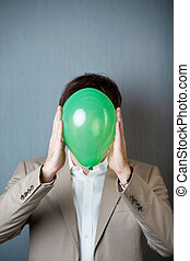 Businessman Holding Balloon In Front Of Face Against Blue Wall