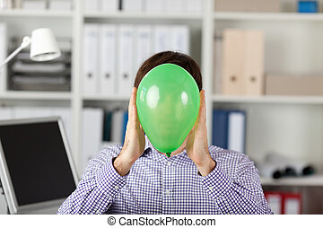 Businessman Holding Balloon In Front Of Face