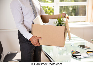 Midsection View Of A Businessman's Hand Holding Belongings In Cardboard Box