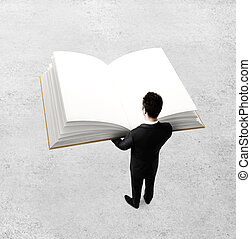 businessman holding big book on gray background