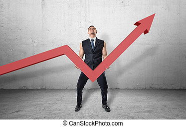 Businessman holding big red line graph with an upturned arrow and trying to raise it up