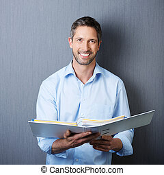 Businessman Holding Binder Against Blue Wall