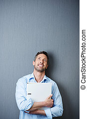Businessman Holding Binder While Looking Up Against Blue Wall