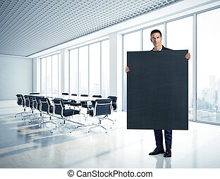Businessman holding blackboard at office
