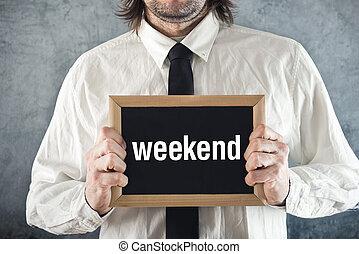 Businessman holding blackboard with WEEKEND title