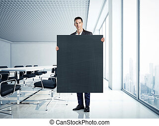 Businessman holding blank blackboard at contemporary office...