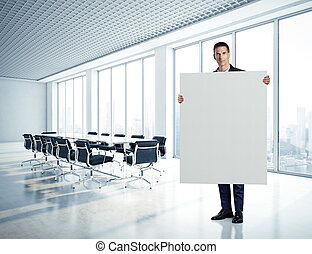 Businessman holding blank canvas at contemporary office