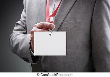 Businessman holding blank ID badge - Businessman at an...