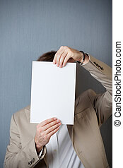Businessman Holding Blank Paper In Front Of Face
