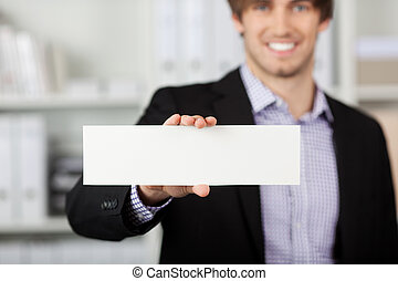 Businessman Holding Blank Paper In Office