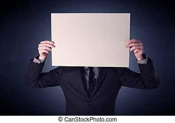 Businessman holding blank paper - Young businessman hiding...
