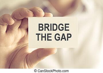 Businessman holding BRIDGE THE GAP message card