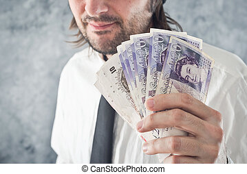 Businessman holding British pounds money. Paying with...