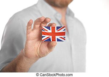 Businessman holding business card with United Kingdom flag -...