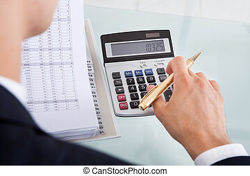 Businessman Holding Calculating Expense In Office - Cropped...