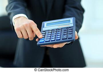 Businessman holding calculator.