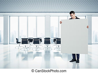 Businessman holding canvas at contemporary office
