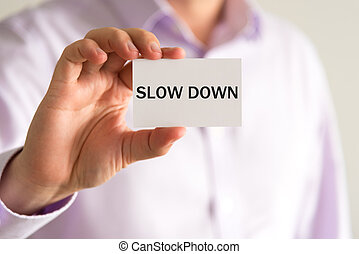Businessman holding card with text SLOW DOWN