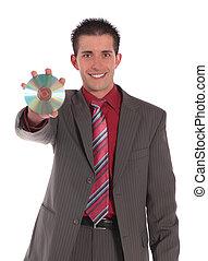 Businessman holding CD or DVD - A handsome businessman...