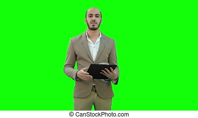 Businessman holding clipboard and presenting business report on a Green Screen, Chroma Key.