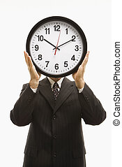 Businessman holding clock.