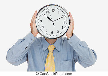 Businessman holding clock in front of face