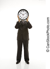 Businessman holding clock.