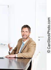 Businessman Holding Coffee Cup At Desk In Office