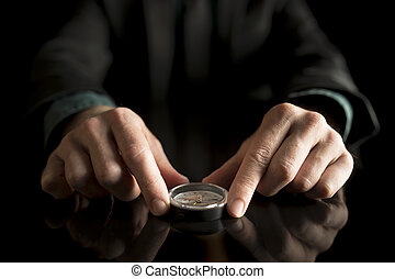 Businessman holding compass on a black table