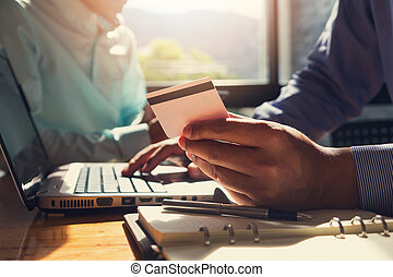 Businessman holding credit card and using laptop to shopping online