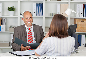Businessman Holding Cv Of Female Candidate At Desk - Mature...