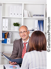 Businessman Holding Cv With Female Candidate At Desk