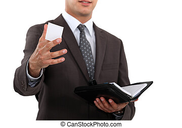 Businessman holding diary and offering business card