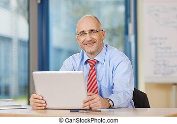 Businessman Holding Digital Tablet At Office Desk