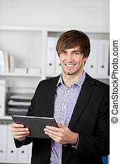 Businessman Holding Digital Tablet In Office