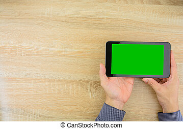 Businessman holding digital tablet with green screen.