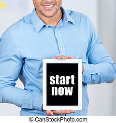 Businessman Holding Digital Tablet With Start Now Sign