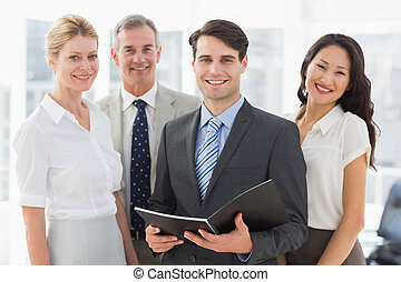 Businessman holding document smiling at camera with his team